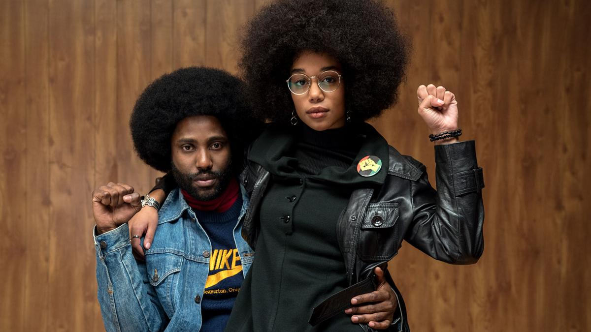 Laura Harrier as Patrice Dumas with John David Washington, both displaying Black Power fists